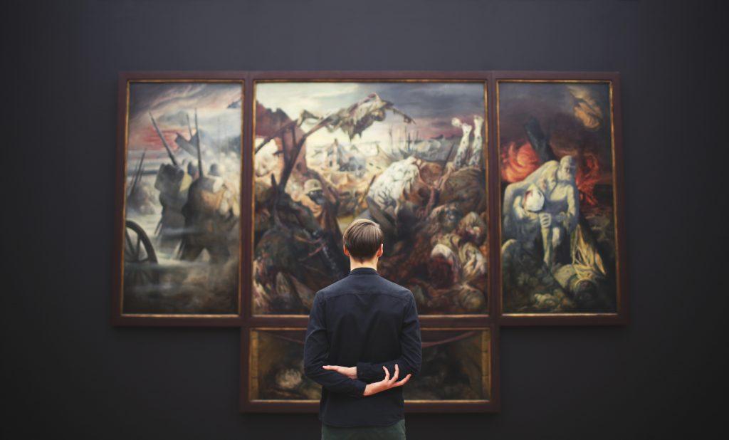 Home observant un quadre en un museu